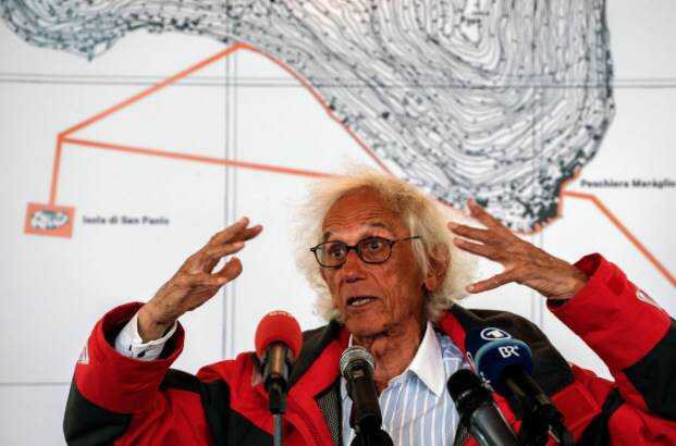 The artist Christo at last weeks press conference for his latest major project 'Floating Piers' with a partial map of Lake Iseo in the background